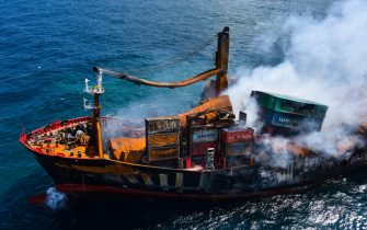 epa09243155 A handout photo made available by the Sri Lankan Air force Mediashows thefire gutted and crippled Singapore-registered container cargo vessel, MV X-Press Pearl, on the9 nautical miles northwest of Colombo port in Colombo, Sri Lanka, 02 June 2021. The fire on the Singaporean flagged container cargo vessel MV X-Press Pearl, which had been burning for over 13 days, was doused and the salvage company began towing it towards deeper seas off the coast of Colombo on 02 June. However, latest reports by the Sri Lanka Navy stated that the towing operation had been halted as the stern of the ship was striking the seabed. They also reported that so far no oil spills have been observed. A huge amount of plastic granules and debris has already washed ashore on beaches from Colombo to Negombo and authorities now fear another wave of massive pollution should the 278 tonnes of bunker oil and 50 tonnes of gas in the Singapore-registered ship's fuel tanks leak into the Indian Ocean.  EPA/SRI LANKAN AIR FORCE MEDIA HANDOUT  HANDOUT EDITORIAL USE ONLY/NO SALES