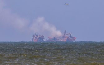 epa09242444 Smoke rises from the fire gutted and crippled container cargo vessel MV X-Press Pearl in Sri Lanka, 02 June 2021. The fire on the Singaporean flagged container cargo vessel MV X-Press Pearl, which had been burning for over 13 days, was doused and the salvage company began towing it towards deeper seas off the coast of Colombo on 02 June. However, latest reports by the Sri Lanka Navy stated that the towing operation had been halted as the stern of the ship was striking the seabed. They also reported that so far no oil spills have been observed. A huge amount of plastic granules and debris has already washed ashore on beaches from Colombo to Negombo and authorities now fear another wave of massive pollution should the 278 tonnes of bunker oil and 50 tonnes of gas in the Singapore-registered ship's fuel tanks leak into the Indian Ocean.  EPA/CHAMILA KARUNARATHNE