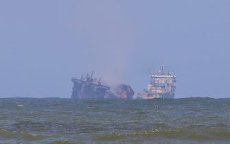 epa09242440 A ship from the Dutch salvage company SMIT (R) towing the fire gutted and crippled container cargo vessel MV X-Press Pearl to deeper seas off the port of Colombo, Sri Lanka, 02 June 2021. The fire on the Singaporean flagged container cargo vessel MV X-Press Pearl, which had been burning for over 13 days, was doused and the salvage company began towing it towards deeper seas off the coast of Colombo on 02 June. However, latest reports by the Sri Lanka Navy stated that the towing operation had been halted as the stern of the ship was striking the seabed. They also reported that so far no oil spills have been observed. A huge amount of plastic granules and debris has already washed ashore on beaches from Colombo to Negombo and authorities now fear another wave of massive pollution should the 278 tonnes of bunker oil and 50 tonnes of gas in the Singapore-registered ship's fuel tanks leak into the Indian Ocean.  EPA/CHAMILA KARUNARATHNE