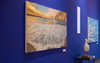 """Un'onda finisce la sua corsa sulla battigia in una foto esposta alla mostra """"Il mare chiama chi ama ilmare"""""""