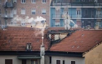Fumo esce da alcune canne fumarie di edifici del centro di Milano, 14 gennaio 2020. La Regione Lombardia ha deciso di anticipare a domani le misure di secondo livello del protocollo aria a causa del sequenza di superamento di livelli limite di Pm10 nell'aria. ANSA/MATTEO CORNER