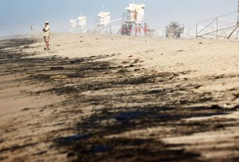 HUNTINGTON BEACH, CALIFORNIA - OCTOBER 03: A person stands near oil washed up on Huntington State Beach after a 126,000-gallon oil spill from an offshore oil platform on October 3, 2021 in Huntington Beach, California. The spill forced the closure of the popular Great Pacific Airshow with authorities urging people to avoid beaches in the vicinity.  (Photo by Mario Tama/Getty Images)