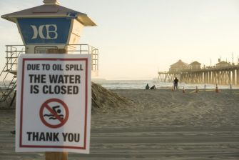 HUNTINGTON BEACH, CALIFORNIA - OCTOBER 03: A warning sign is posted near oil washed up on Huntington State Beach after a 126,000-gallon oil spill from an offshore oil platform on October 3, 2021 in Huntington Beach, California. The spill forced the closure of the popular Great Pacific Airshow with authorities urging people to avoid beaches in the vicinity. (Photo by Sefa Degirmenci/Anadolu Agency via Getty Images)