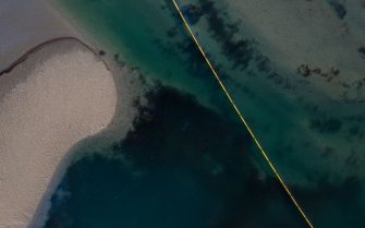 """This aerial picture taken on October 3, 2021 shows oil and an oil containment boom in the water of the Talbert Marshlands area from an offshore oil rig as it reaches the shore and sensitive wildlife habitats in Newport Beach, California. - Authorities in California's beachfront Orange County cities scrambled  October 3, 2021 to mitigate the fallout from a major oil spill off the coast that caused """"substantial ecological impacts.""""  As of Sunday, the oil plume from the 126,000-gallon (480,000 liters) spill of post-production crude was an estimated 5.8 nautical miles (6.7 miles, 10 kilometers) long and stretched along the popular shorelines of Huntington Beach and Newport Beach, Huntington Beach city authorities said in a statement. (Photo by DAVID MCNEW / AFP) (Photo by DAVID MCNEW/AFP via Getty Images)"""