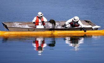 HUNTINGTON BEACH, CALIFORNIA - OCTOBER 03: Cleanup workers attempt to contain oil which seeped into Talbert Marsh, which is home to around 90 bird species, after a 126,000-gallon oil spill from an offshore oil platform on October 3, 2021 in Huntington Beach, California. The spill forced the closure of the popular Great Pacific Airshow with authorities urging people to avoid beaches in the vicinity.  (Photo by Mario Tama/Getty Images)