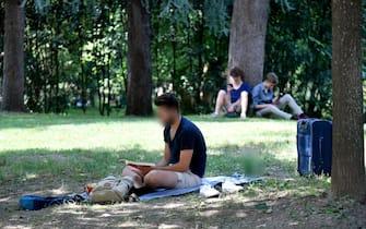 Una persona legge un libro all'ombra degli alberi in un parco del centro di Milano, 1 agosto 2019. ANSA/DANIEL DAL ZENNARO