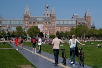 AMSTERDAM, NETHERLANDS - MAY 9: A couple push bicycles through the Museumplein as Rijksmuseum, which is currently closed due to the coronavirus (COVID-19) pandemic, is seen in the background on May 9, 2020 in Amsterdam, Netherlands. (Photo by Yuriko Nakao/Getty Images)
