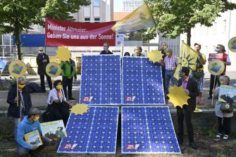 "Activists hold a placard reading ""Minister Altmeier: go from sun!"" and diaplay lookalike solar panels during a protest to call the government to ease up the production of climate-friendly solar power, in Berlin, on September 3, 2020. (Photo by John MACDOUGALL / AFP) (Photo by JOHN MACDOUGALL/AFP via Getty Images)"