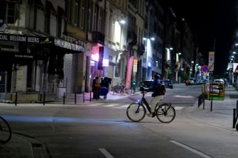 BRUSSELS, BELGIUM - OCTOBER 20 :  A cyclist rides through the streets during a curfew on October 20, 2020 in the Etterbeek municipality of the Brussels-Capital Region, Belgium. New stricter measures begin today after the country was placed on alert Level 4 of the COVID-19 barometer. A curfew is in place from midnight until 5 a.m. and all bars and restaurants are closed for four weeks. Hospitals are under increasing pressure as the number of coronavirus patients in intensive care is 2.5 times higher today than at the end of March. Schools have been shut down as has much of the economy due to the widespread lockdown. (Photo by Thierry Monasse/Getty Images)