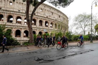 Cyclists ride over potholes on a road past the Colosseum in downtown Rome on April 12, 2018. - Romes roads problems have been existing for years, due to structural failures as the city's basement is historically riddled with natural cavities. As a result, potholes range from a few centimeters deep to several meters that severely disrupt traffic and sometimes cause spectacular car accidents. (Photo by Andreas SOLARO / AFP)        (Photo credit should read ANDREAS SOLARO/AFP via Getty Images)