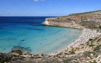 Tourists are pictured on the beach of the Isola dei Conigli (Rabbit Island) in Lampedusa on September 27, 2018. - Five years after the worst shipwreck of its history, the Italian Pelagie Island of Lampedusa relies on the flood of tourists to make a fresh start, though it might become a gateway to Europe again. (Photo by Alberto PIZZOLI / AFP) / TO GO WITH AFP STORY BY FANNY CARRIER        (Photo credit should read ALBERTO PIZZOLI/AFP via Getty Images)