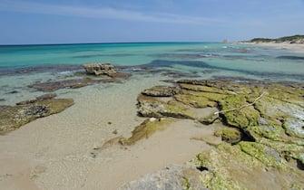 Alcue rocce emergono dal mare vicino alla spiaggia di Pilone, vicino a Ostuni, Puglia