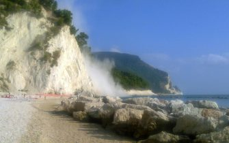 Handout image released by Italian port captaincy on 22 August 2013 shows the smoke raised by the collapse of a limestone block that broke off from the Monte Conero, falling between the beach and the Lavi Lilies of Ancona, in coincidence of the 4.4 earthquake in the Marches, 22 August 2013.  ANSA/ UFFICIO STAMPA CAPITANERIA PORTO ANCONA ++HO - NO SALES EDITORIAL US EONLY++