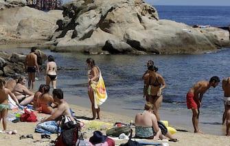 Bagnanti e turisti sulla spiaggia vicino al Porto del Giglio dopo la rimozione della Costa Concordia, Isola del Giglio,  24 luglio 2014. ANSA/RICCARDO ANTIMIANI
