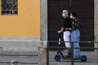 A couple wearing a face mask rides an electric scooter along a Navigli canal in Milan on May 8, 2020 during the country's lockdown aimed at curbing the spread of the COVID-19 infection, caused by the novel coronavirus. (Photo by Miguel MEDINA / AFP) (Photo by MIGUEL MEDINA/AFP via Getty Images)