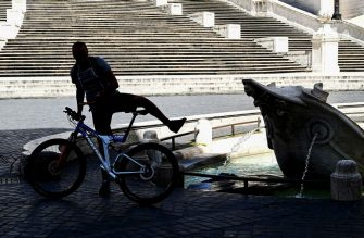 A man gets on his bicycle by the Fontana della Barcaccia at the bottom of the Spanish Steps in central Rome on May 8, 2020, during the country's lockdown aimed at curbing the spread of the COVID-19 infection, caused by the novel coronavirus. (Photo by Vincenzo PINTO / AFP) (Photo by VINCENZO PINTO/AFP via Getty Images)
