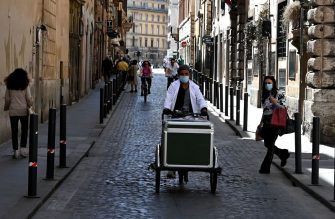 A man wearing a protective face mask rides a delivery bicycle down a narrow street in Rome on May 9, 2020, during the country's partial lockdown aimed at curbing the spread of the COVID-19 infection, caused by the novel coronavirus. (Photo by Tiziana FABI / AFP) (Photo by TIZIANA FABI/AFP via Getty Images)