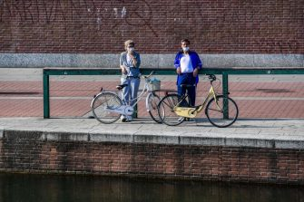People wearing a face mask stand with their bicycle along the Navigli canals in Milan on May 8, 2020 during the country's lockdown aimed at curbing the spread of the COVID-19 infection, caused by the novel coronavirus. (Photo by Miguel MEDINA / AFP) (Photo by MIGUEL MEDINA/AFP via Getty Images)