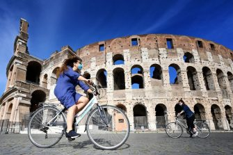 TOPSHOT - Women ride a bicycle past the Colosseum monument in Rome on May 8, 2020, during the country's lockdown aimed at curbing the spread of the COVID-19 infection, caused by the novel coronavirus. - The number of deaths from coronavirus in Italy now exceeds 30,000, officials said on May 8, 2020. The country's Civil Protection Agency said that 30,201 people had died of the virus, 243 more than on May 7. Italy is the second European country, after Britain to see more than 30,000 COVID-19 deaths. (Photo by Alberto PIZZOLI / AFP) (Photo by ALBERTO PIZZOLI/AFP via Getty Images)