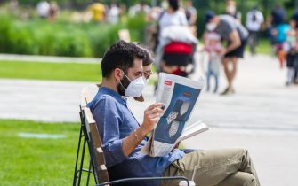 MILAN, ITALY - MAY 10: A couple intent on reading on a benchin CityLife Park during the first sunday of phase two of the containment of the pandemic from Covid-19  on May 10, 2020 in Milan, Italy. Italy was the first country to impose a nationwide lockdown to stem the transmission of the Coronavirus (Covid-19), and its restaurants, theaters and many other businesses remain closed. (Photo by Roberto Finizio/Getty Images)