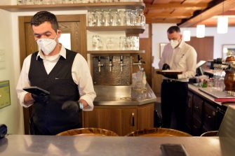 BOLZANO, ITALY - MAY 11: Waiters wear face masks at work in the restaurant after today's business reopening on May 11, 2020 in Bolzano, Italy. The Bolzano province started the reopening of some businesses one week earlier than the rest of Italy, arising many controversies. (Photo by Alessio Coser/Getty Images)