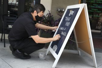 PALM BEACH, FLORIDA - MAY 11: Gary Tharitimanont uses a chalk board to let patrons know his Peppermint Downtown Thai restaurant is open on May 11, 2020 in Palm Beach, Florida. The restaueant opened as Palm Beach County, starts the first phase of the states coronavirus pandemic reopening plan, which includes  openings of businesses, with certain caveats, like barbershops, restaurants and retail stores. (Photo by Joe Raedle/Getty Images)