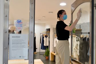 BOLZANO, ITALY - MAY 11: A saleswoman cleans the shop window after the reopening of the business today on May 11, 2020 in Bolzano, Italy. The Bolzano province started the reopening of some businesses one week earlier than the rest of Italy, arising many controversies. (Photo by Alessio Coser/Getty Images)