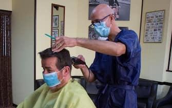 Un parrucchiere taglia i capelli ad un cliente nel suo negozio per la fase 2 della pandemia che prevede una graduale apertura delle attività commerciali a Carbonia, 11 Maggio 2020 ANSA/ FABIO MURRU