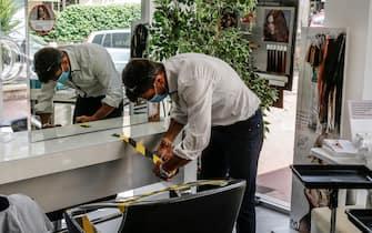 Il parrucchiere Pietro Galante ed i suoi collaboratori preparano il locale per la riapertura sistemando nastri, guanti, mascherine e divisori in plaxiglas per garantire la sicurazza ad i propri clienti e combattere la diffusione del coronavirus, Roma 11 maggio 2020.  ANSA / FABIO FRUSTACI