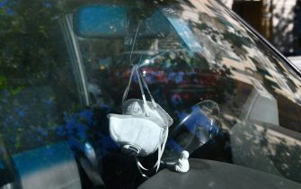 Due mascherine con filtro appese allo specchietto retrovisore di un'auto.. Genova, 30 Aprile 2020. ANSA/LUCA ZENNARO