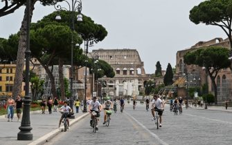 People ride their bicycles along the Fori Imperiali street in central Rome on May 17, 2020 during the country's lockdown aimed at curbing the spread of the COVID-19 infection, caused by the novel coronavirus. (Photo by Andreas SOLARO / AFP) (Photo by ANDREAS SOLARO/AFP via Getty Images)