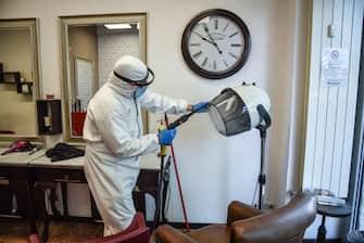 Operatori in tuta bianca sanificano un negozio per parrucchiere in vista della riapertura dopo il lockdown per l emergenza del coronavirus, Milano, 07 maggio 2020.  Ansa/Matteo Corner