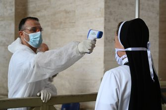 A nun undergoes body temperature scanning while going through security to access St. Peter's Square and Basilica on May 18, 2020 in The Vatican during the lockdown aimed at curbing the spread of the COVID-19 infection, caused by the novel coronavirus. - Saint Peter's Basilica throws its doors open to visitors on May 18, 2020, marking a relative return to normality at the Vatican and beyond in Italy, where most business activity is set to resume. (Photo by Vincenzo PINTO / AFP) (Photo by VINCENZO PINTO/AFP via Getty Images)