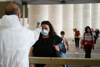 A woman undergoes body temperature scanning while going through security to access St. Peter's Square and Basilica on May 18, 2020 in The Vatican during the lockdown aimed at curbing the spread of the COVID-19 infection, caused by the novel coronavirus. - Saint Peter's Basilica throws its doors open to visitors on May 18, 2020, marking a relative return to normality at the Vatican and beyond in Italy, where most business activity is set to resume. (Photo by Vincenzo PINTO / AFP) (Photo by VINCENZO PINTO/AFP via Getty Images)
