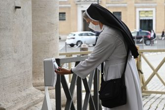 A nun sanitizes her hands while going through security to access St. Peter's Square and Basilica on May 18, 2020 in The Vatican during the lockdown aimed at curbing the spread of the COVID-19 infection, caused by the novel coronavirus. - Saint Peter's Basilica throws its doors open to visitors on May 18, 2020, marking a relative return to normality at the Vatican and beyond in Italy, where most business activity is set to resume. (Photo by Vincenzo PINTO / AFP) (Photo by VINCENZO PINTO/AFP via Getty Images)