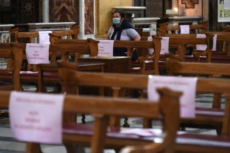 """A woman attends mass at the church of Santa Maria in Traspontina in Rome on May 18, 2020 during the country's lockdown aimed at curbing the spread of the COVID-19 infection, caused by the novel coronavirus. - Restaurants and churches reopen in Italy on May 18, 2020 as part of a fresh wave of lockdown easing in Europe and the country's latest step in a cautious, gradual return to normality, allowing businesses and churches to reopen after a two-month lockdown. Placards read """"Security distancing, do not seat in this space"""". (Photo by Vincenzo PINTO / AFP) (Photo by VINCENZO PINTO/AFP via Getty Images)"""