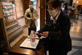 A woman wearing a face mask cleans her hands with sanitizer prior to a mass at the church of Santa Maria in Traspontina in Rome on May 18, 2020 during the country's lockdown aimed at curbing the spread of the COVID-19 infection, caused by the novel coronavirus. - Restaurants and churches reopen in Italy on May 18, 2020 as part of a fresh wave of lockdown easing in Europe and the country's latest step in a cautious, gradual return to normality, allowing businesses and churches to reopen after a two-month lockdown. (Photo by Vincenzo PINTO / AFP) (Photo by VINCENZO PINTO/AFP via Getty Images)