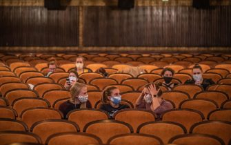 epa08415463 People wearing protective face masks wait for screening as they sit in a reopened cinema in the centre of Prague, Czech Republic, 11 May 2020. Cinemas across the country are allowed to play again with maximum attendance of 100 people from 11 May 2020 as next wave of Czech government's easing the restrictive measures declared to quell the spread of the pandemic COVID-19 disease caused by the SARS-CoV-2 coronavirus.  EPA/MARTIN DIVISEK