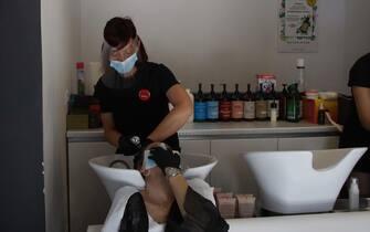 Una donna lava i capelli dal parrucchiere