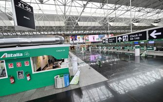 A general view shows Alitalia check-in counters in a deserted Terminal T1 at Rome's Fiumicino international airport on March 17, 2020. - Rome's second airport, Ciampino, has been closed, while Fiumicino is to close the T1, one of its three terminals from March 17. (Photo by ANDREAS SOLARO / AFP)