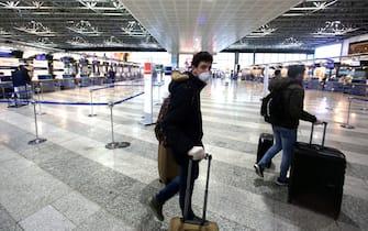 Alcuni viaggiatori in attesa del volo all'aeroporto di Milano Malpensa. Milano 09 Marzo 2020.ANSA / MATTEO BAZZI