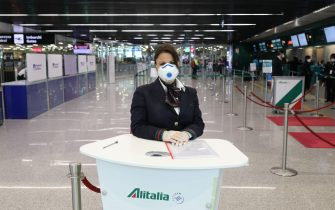 ROME, ITALY - MARCH 17: A ground assistant of the Alitalia airline company wearing a protective mask is seen waiting to assist passengers at Terminal 3 of the Leonardo Da Vinci international airport of Rome Fiumicino on March 17, 2020 in Rome, Italy. One of the two terminals of the Leonardo Da Vinci international airport of Rome Fiumicino, the terminal 1 usually dedicated to domestic flights closes temporarily due to the Coronavirus emergency, the little air traffic left has been moved to Terminal 3. (Photo by Marco Di Lauro/Getty Images)