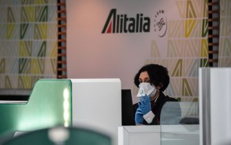 An airport Alitalia staff, wearing a respiratory mask and gloves, looks on at Rome's Fiumicino international airport March 13, 2020. - Rome's Ciampino airport will shut to passenger flights from March 13, authorities said, with a Terminal T1 also closing at the city's main Fiumicino facility next week as airlines slash flights to Italy over the coronavirus outbreak. (Photo by Andreas SOLARO / AFP) (Photo by ANDREAS SOLARO/AFP via Getty Images)