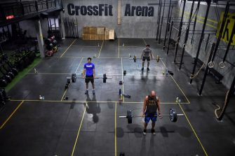 Gym enthusiasts do deadlifts whilst maintaining distance from each other at CrossFit Arena Bangkok, during their first week of reopening following closure of physical wellness centers after authorities lifted some measures of restrictions to halt the spread of the COVID-19 coronavirus in Bangkok on May 20, 2020. (Photo by Lillian SUWANRUMPHA / AFP) (Photo by LILLIAN SUWANRUMPHA/AFP via Getty Images)