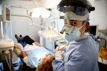 ROME, ITALY - MAY 21: Dentist Fabio Presutti, wearing personal protective equipment (PPE / EPI), treats a patient at 'Studio Mura' on May 21, 2020 in Rome, Italy. Restaurants, bars, cafes, hairdressers and other shops have reopened, subject to social distancing measures, after more than two months of a nationwide lockdown meant to curb the spread of Covid-19. (Photo by Franco Origlia/Getty Images)