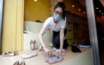 Una commessa di un negozio di scarpe riallestisce la vetrina in vista delle riaperture del 18 maggio durante la fase 2 dell'emergenza Coronavirus a Milano, 14 maggio 2020.ANSA/Mourad Balti Touati