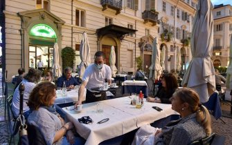 Persone nei dehor dei locali della movida in piazza Carignano nel primo giorno di riapertura, Torino, 23 Maggio 2020 ANSA/ ALESSANDRO DI MARCO