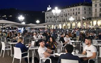 Persone nei dehor dei locali della movida in piazza Vittorio nel primo giorno di riapertura, Torino, 23 Maggio 2020 ANSA/ ALESSANDRO DI MARCO