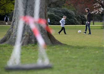 HAMBURG, GERMANY - APRIL 04: Boys play football behind a swing that is no longer allowed to be used next the Aussenalster during the coronavirus crisis on April 4 in Hamburg, Germany. The coronavirus and the disease it causes, Covid-19, are having a fundamental impact on society, government and the economy in Germany. Public life has been restricted to the essentials in an effort by authorities to slow the spread of infections. Hospitals are scrambling to increase their testing and care capacity. An economic recession seems likely as economic activity is slowed and many businesses are temporarily closed. Schools, daycare centers and universities remain shuttered. And government, both federal and state, seek to mobilize resources and find adequate policies to confront the virus and mitigate its impact. (Photo by Stuart Franklin/Getty Images)