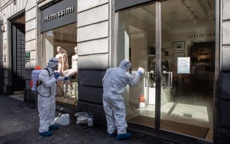 MILAN, ITALY - APRIL 29: Two utility service workers, wearing protective suits, spray sodium hypochlorite to disinfect the window of a women underwear store  on April 29, 2020 in Milan, Italy. Italy will remain on lockdown to stem the transmission of the Coronavirus (Covid-19), slowly easing restrictions. (Photo by Emanuele Cremaschi/Getty Images)